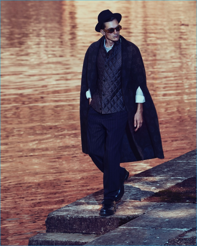 On a stroll, Anthon Wellsjo wears an Ermenegildo Zegna Couture cape, quilted vest, shirt, wool trousers, felt fedora, and leather Derby shoes. The Swedish model also sports Linda Farrow x Dries Van Noten sunglasses.