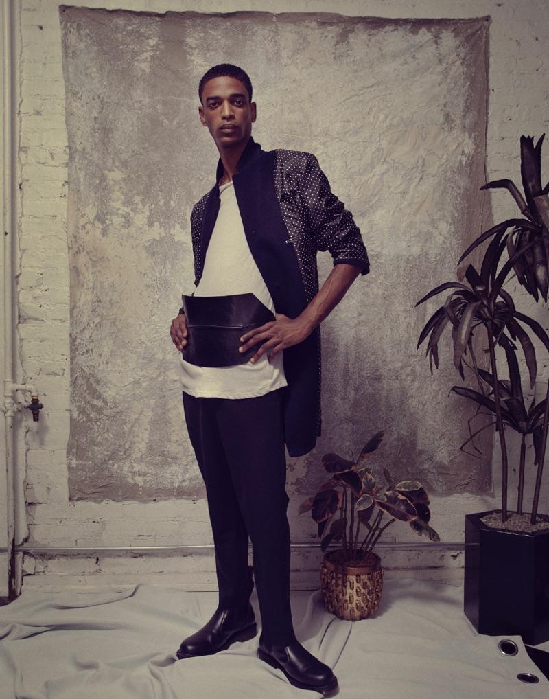 Darron wears coat Spectre & Co., trousers Jil Sander, t-shirt Calvin Klein, belt Ann Demeulemeester, and shoes Dr Martens.