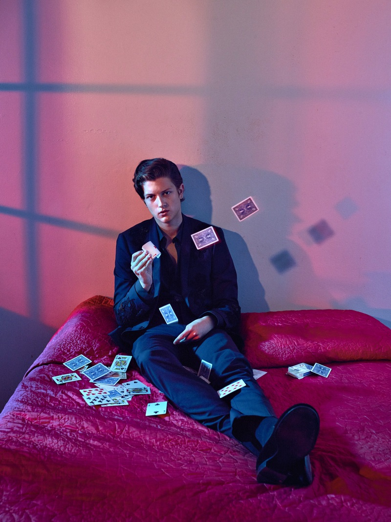 Sam Evans passes time with a deck of playing cards. Going sleek in black, Sam wears a Dolce & Gabbana look with Giuseppe Zanotti shoes.