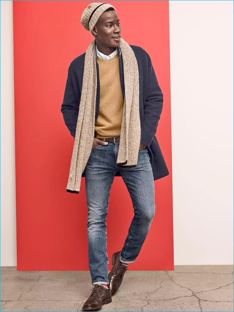 David Agbodji sports a wool coat and camel toned sweater from Gap. The top model also dons distressed denim jeans with a match scarf and knit beanie.