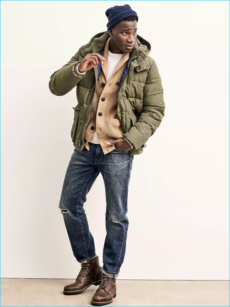 Model David Agbodji wears a puffer jacket with distressed denim jeans, brown leather boots, and a shawl neck cardigan sweater.