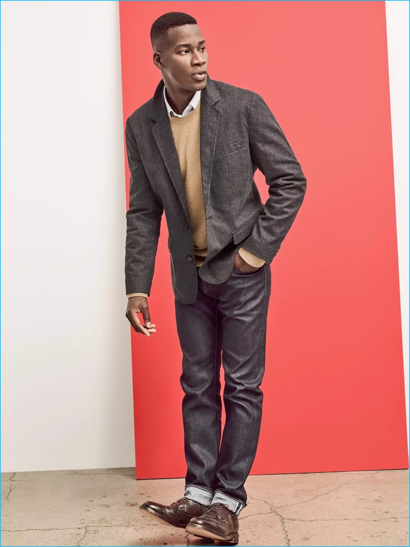 Embracing a smart look, David Agbodji rocks a grey sport coat with a crewneck sweater, smart shirt, and dress shoes.