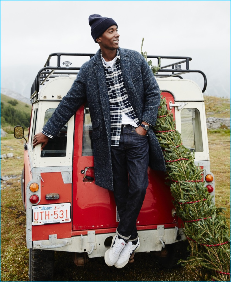 Claudio Monteiro dons an unconstructed Italian herringbone topcoat, Wallace & Barnes blue flannel plaid shirt, and a garment dyed t-shirt from J.Crew. Stepping out in style, Claudio also sports 770 raw selvedge denim jeans, a knit beanie, and Onitsuka Tiger GSM sneakers.