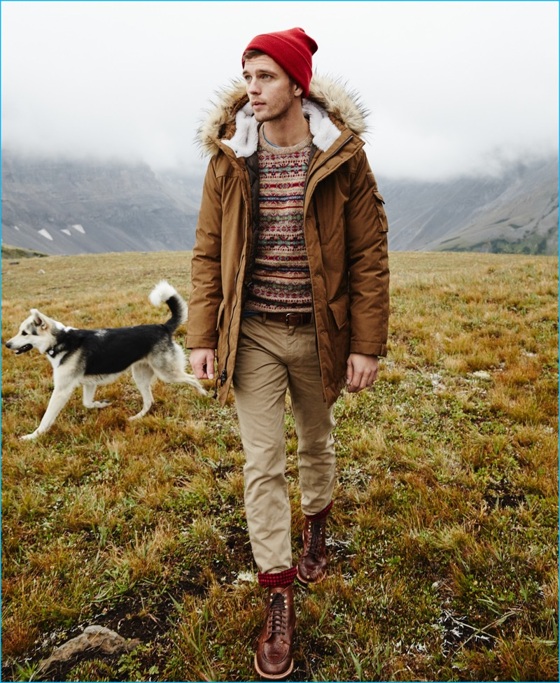 Venturing outdoors, Benjamin Eidem wears J.Crew's Nordic down parka with a fair isle sweater. The top model also sports a Wallace & Barnes indigo pocket t-shirt, 770 chino cabin pants, a red knit beanie, and Kenton leather pacer boots.
