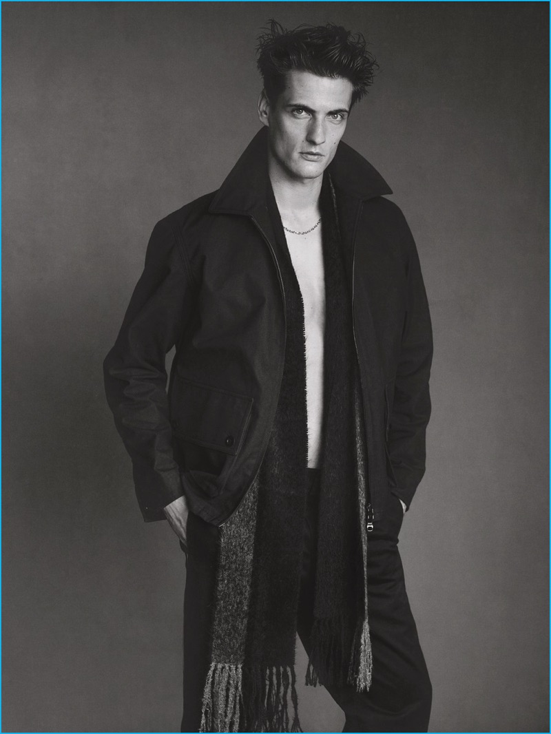 Nicholas Galletti outfits Leo Eller in a Dunhill wool coat, Tommy Hilfiger trousers, and a Bottega Veneta scarf.