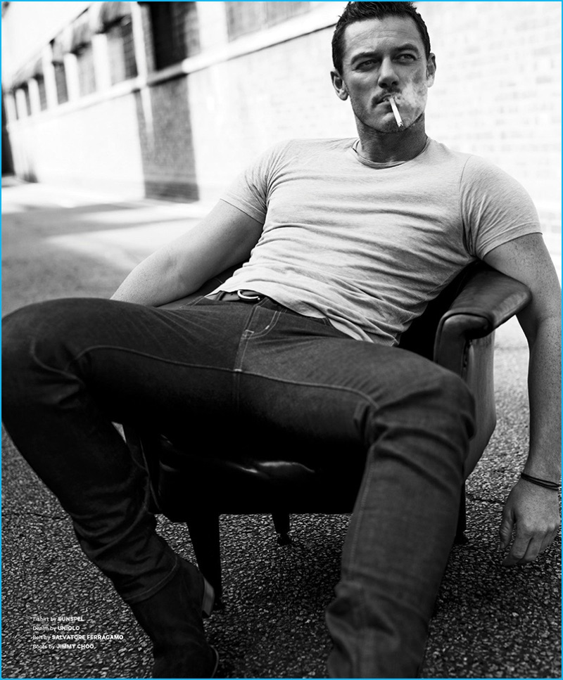 Tom Stubbs outfits Luke Evans in a Sunspel t-shirt and UNIQLO denim jeans with a Salvatore Ferragamo belt and Jimmy Choo boots.