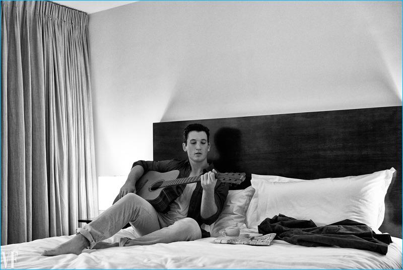 Playing the guitar, Miles Teller wears a Bottega Veneta shirt and Calvin Klein tank with Incotex trousers.