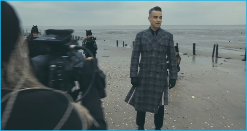 Robbie Williams dons a double-breasted plaid coat by Thom Browne for his Love My Life music video.