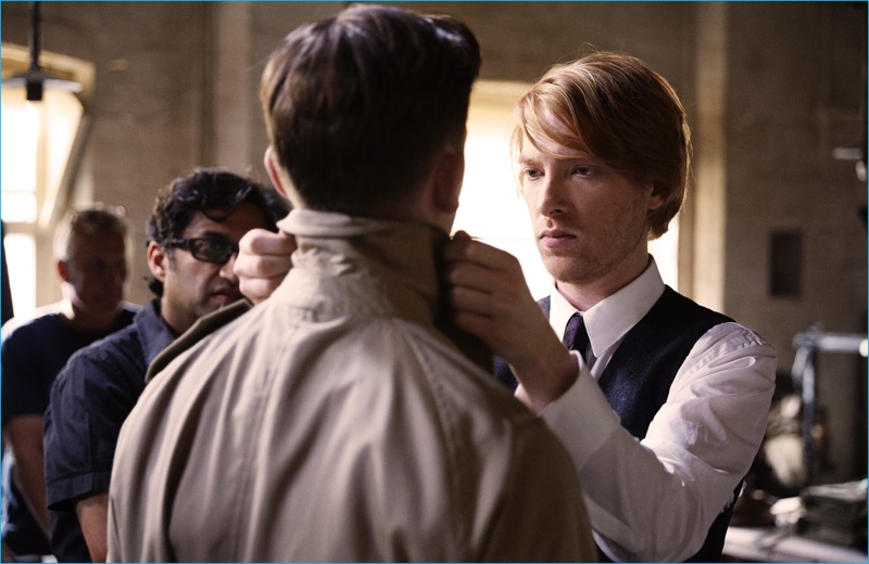 Domhnall Gleeson portrays Thomas Burberry fitting one of his signature trench coats.