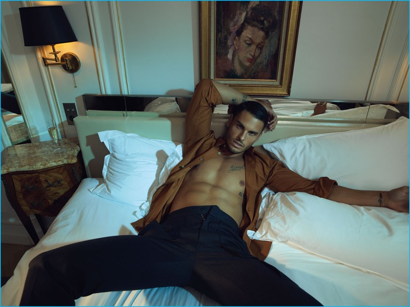 Laying in bed with an open shirt, revealing his six-pack, Baptiste Giabiconi wears Monlada Homme and Louis Vuitton.