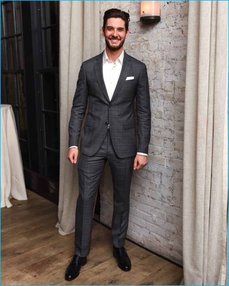 Ben Barnes is all smiles in a charcoal two-button Salvatore Ferragamo suit.