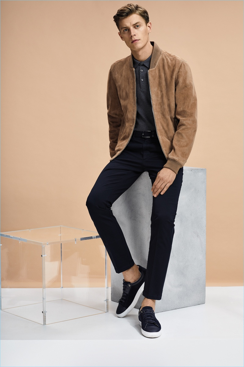 Leading model Janis Ancens sports a suede bomber jacket with a polo shirt, slim-fit pants, and sneakers by BOSS Hugo Boss.