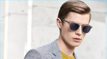 Donning grey shades, Janis Ancens is a sleek vision in a BOSS sportcoat and yellow sweater. The Latvian model also carries a leather portfolio.