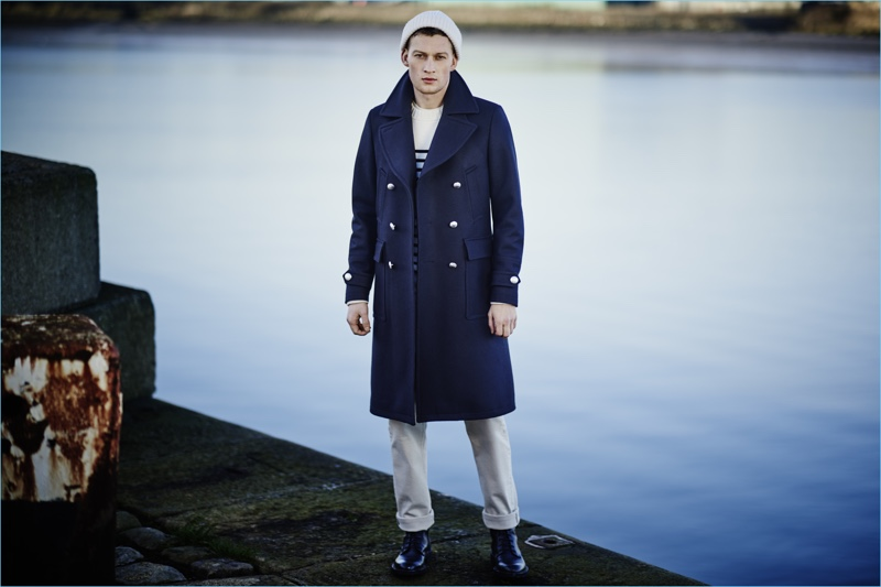 Model Bastian Thiery channels naval style in a navy double-breasted coat by Belstaff.