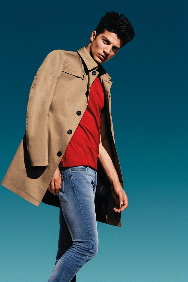 Model Simone Susinna sports a single-breasted coat with a red tee and distressed denim jeans from CINQUE.