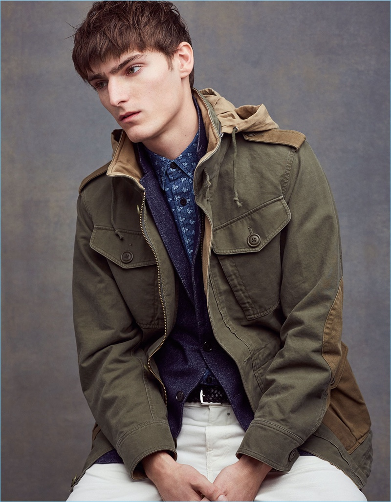 Alexander Beck embraces military style in a military jacket, indigo blazer, chinos, and a printed shirt by Club Monaco.