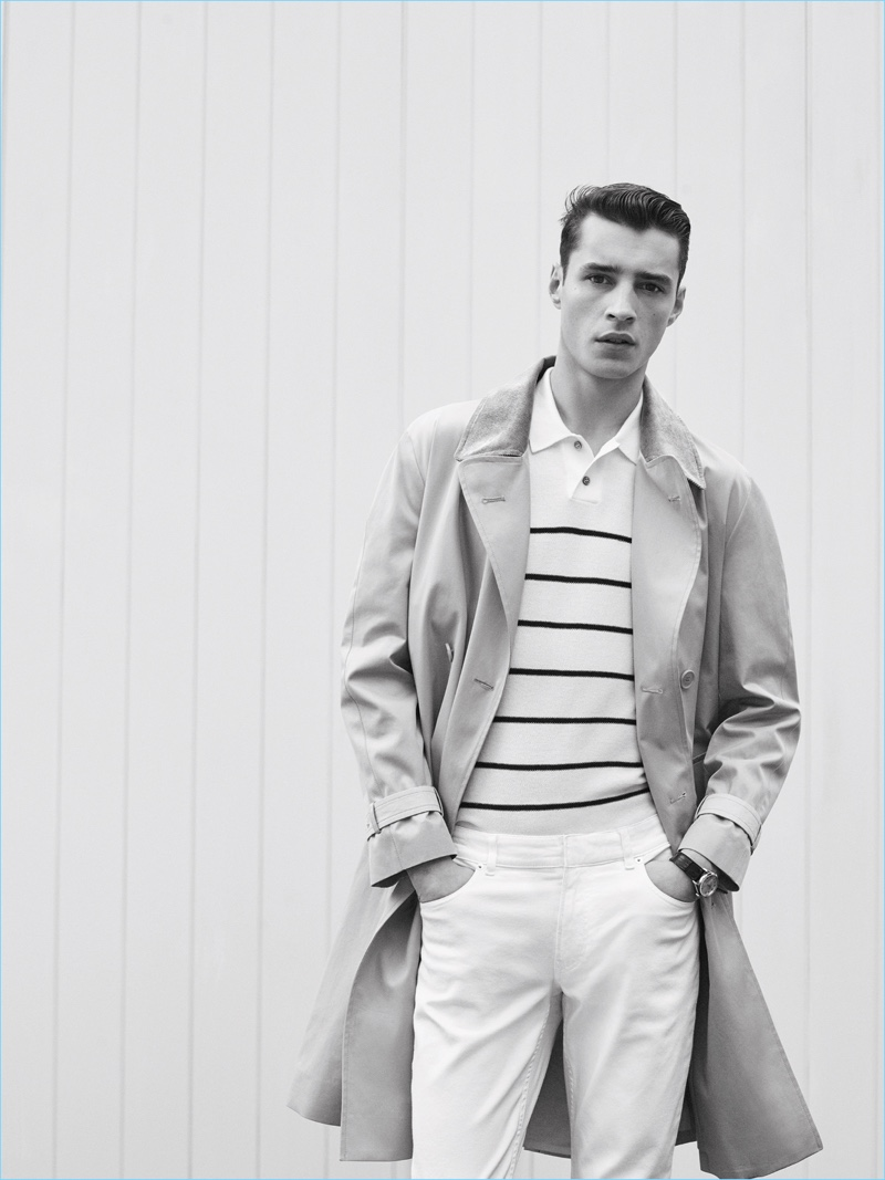 Stepping outdoors, Adrien Sahores wears a trench coat with a striped polo shirt and white pants by De Fursac.
