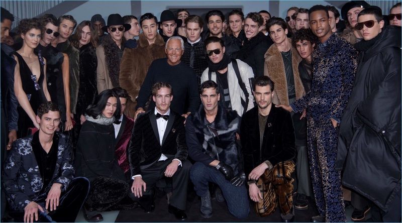 Designer Giorgio Armani poses for pictures with models who walked Emporio Armani's fall-winter 2017 men's show.