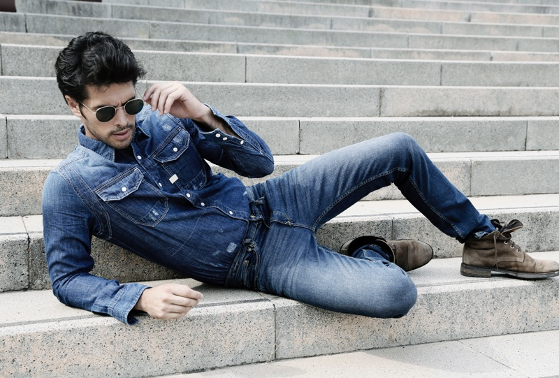 Raul wears denim shirt G-Star Raw, distressed denim jeans GUESS, boots Replay, and aviator sunglasses Ray-Ban.