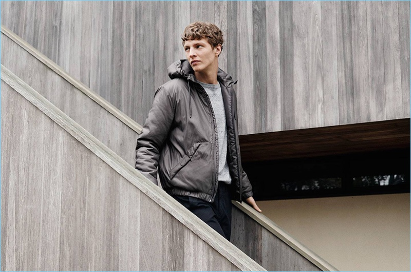 Ready to hit the road, Tim Schuhmacher wears a padded hooded jacket, sweater, and slim-fit pants.