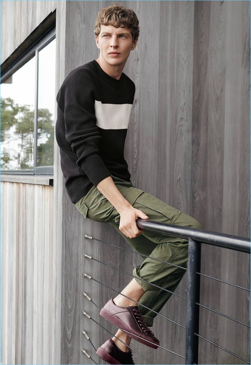 Embracing off-duty style, Tim Schuhmacher models a fine-knit sweater, cargo pants, and sneakers.
