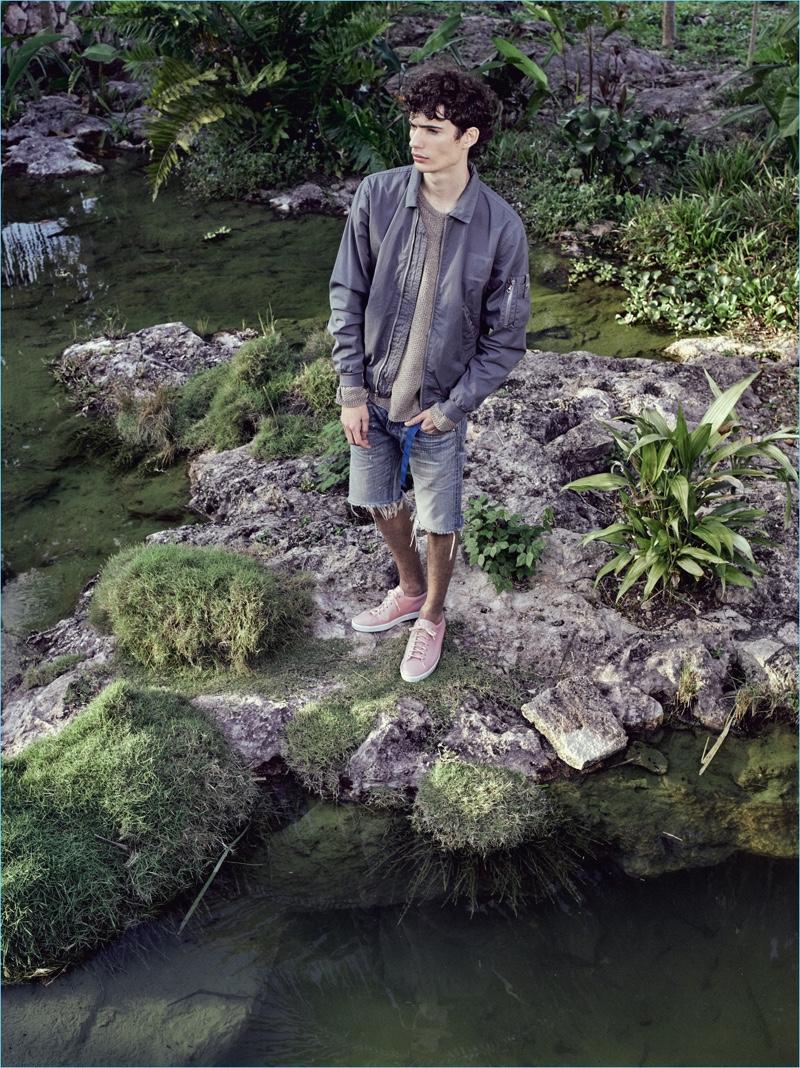 Venturing outdoors, Piero Mendez wears a bomber jacket with frayed denim shorts from John Elliott.