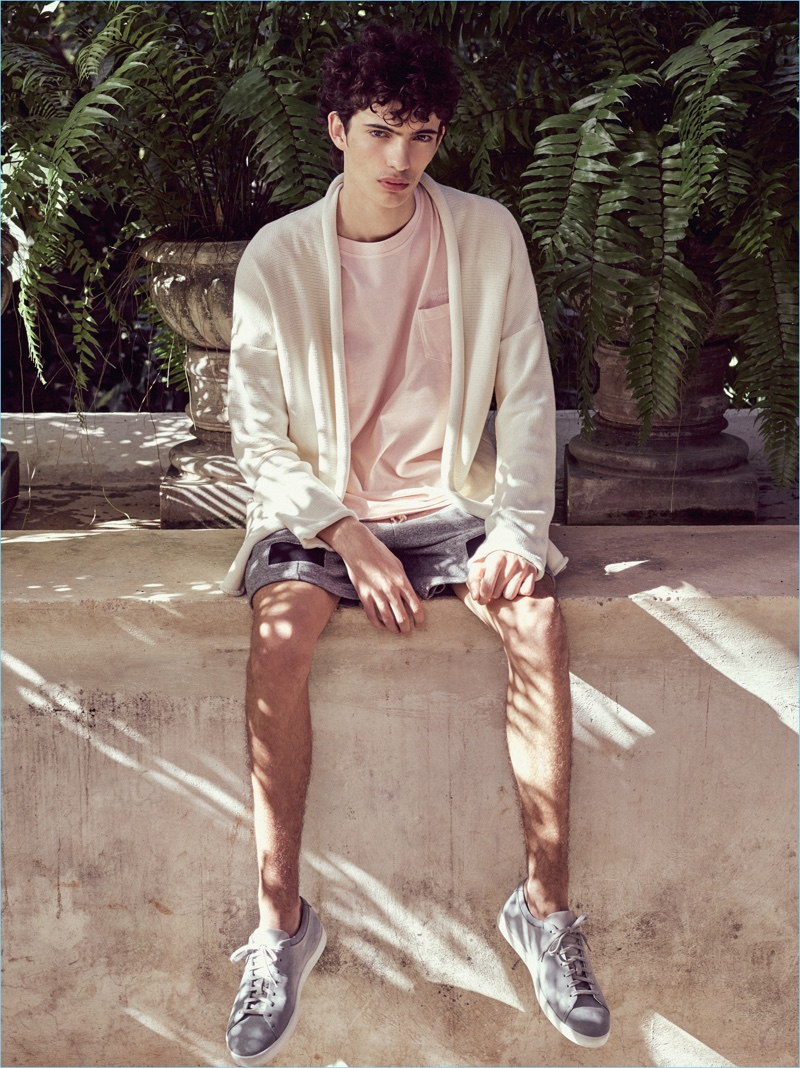 Piero Mendez dons a pale pink pocket tee with a cardigan and shorts by John Elliott.