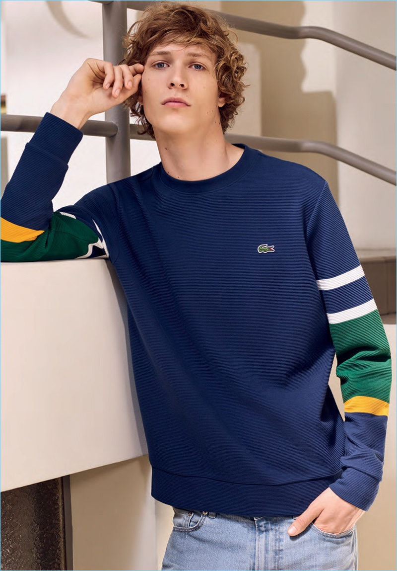 Model Sven de Vries sports a color blocked pullover by Lacoste.