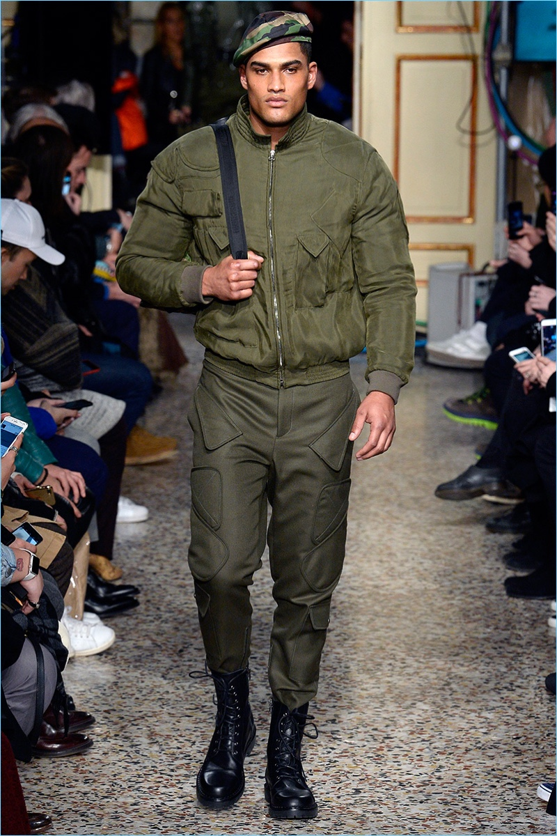 Rob Evans wears an army green bomber jacket and detailed pants from Moschino's fall-winter 2017 men's collection.