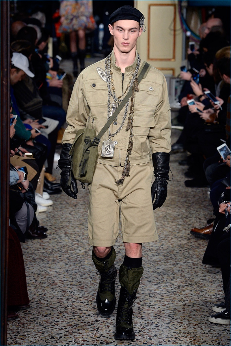 Kit Butler dons a khaki military inspired ensemble from Moschino's fall-winter 2017 men's collection.