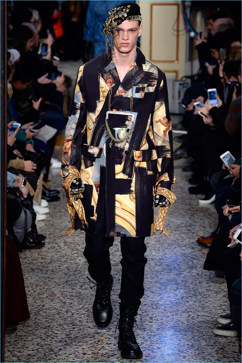 Filip Hrivnak walks the runway in a bold graphic number from Moschino's fall-winter 2017 men's collection.