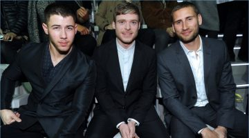 Nick Jonas, Richard Madden, and Edward Holcroft sit front row at Emporio Armani's fall-winter 2017 show.