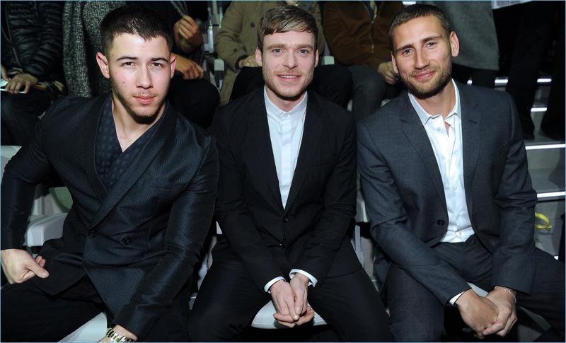 Nick Jonas, Richard Madden, and Edward Holcroft sit front row at Emporio Armani's fall-winter 2017 show.