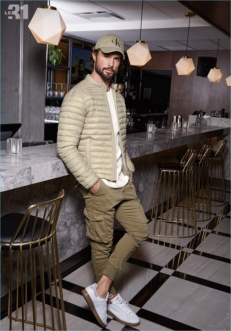 Monochromatic style is front and center as Walter Savage wears a LE 31 quilted jacket, knit sweater, and cargo joggers with a Calvin Klein logo cap. Walter also sports Adidas' essential Stan Smith sneakers.