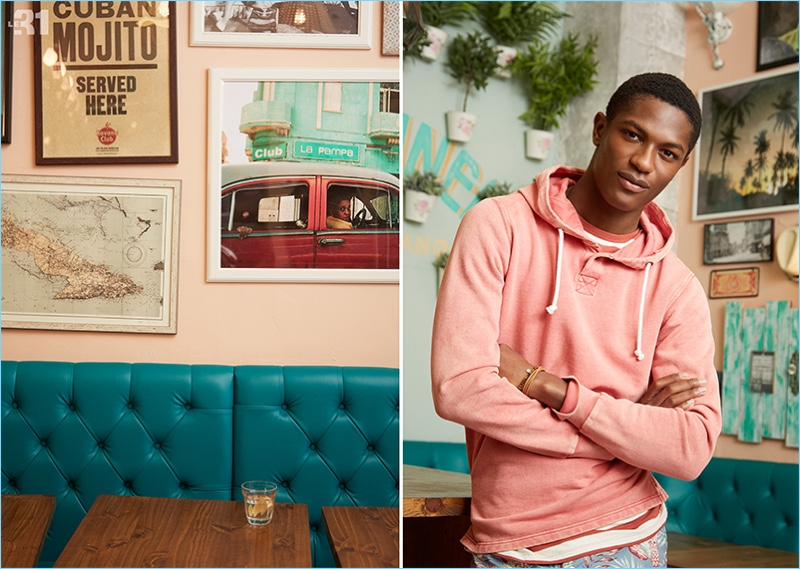 A relaxed vision, Hamid Onifade wears a pale pastel hoodie, striped t-shirt, and floral Bermudas from LE 31.