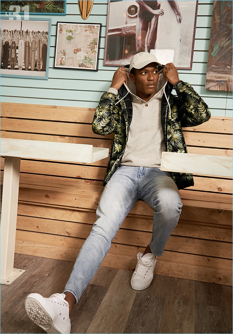 Tackling a sporty ensemble, Hamid Onifade models a LE 31 packable quilted jacket, henley style hoodie, white cap, and distressed denim jeans with Adidas Stan Smith sneakers.