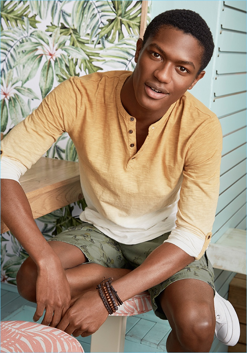 Tapping into the ombré trend, Hamid Onifade wears a gradient colored henley with cargo shorts by LE 31.