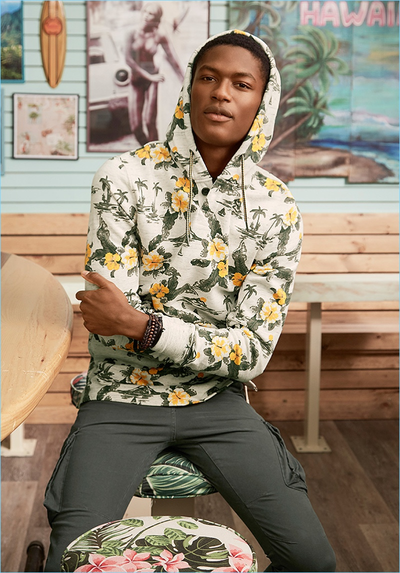 Embracing a tropical flair, Hamid Onifade wears LE 31's Fiji trip floral print hoodie with cargo joggers, and various bracelets.