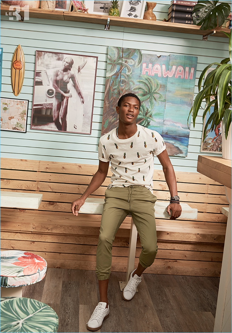 Model Hamid Onifade charms in a pineapple print t-shirt and joggers by LE 31. Hamid also sports Adidas Stan Smith sneakers.