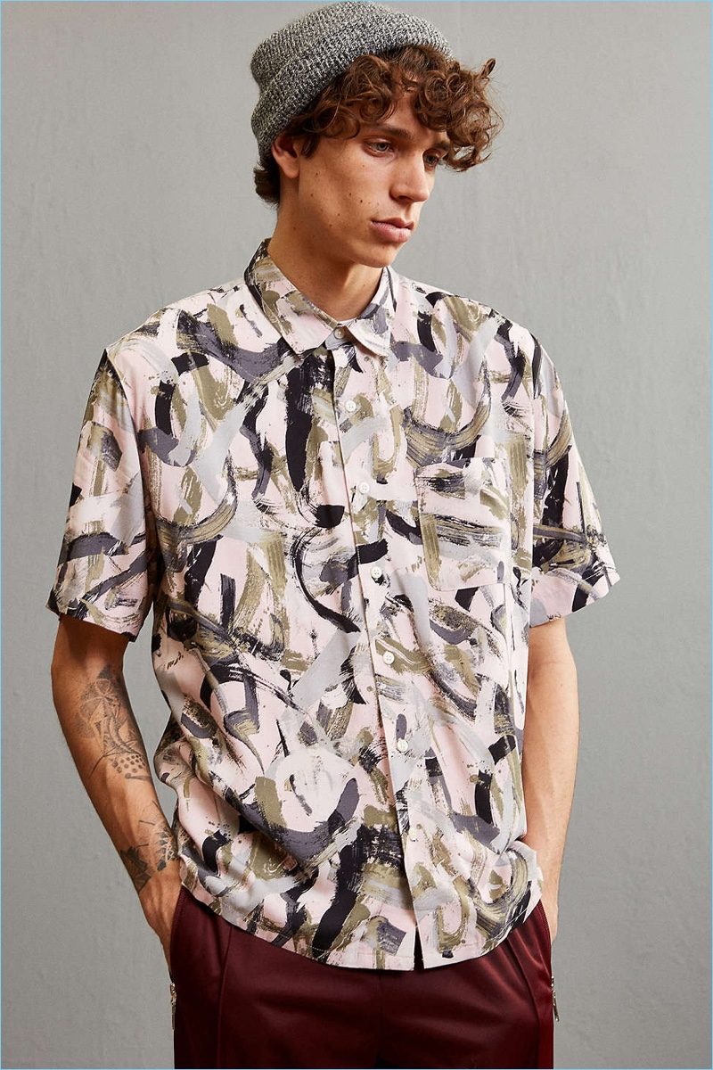 Breezy rayon button-down shirt from Urban Outfitters in an artistic brushstroke print. Lightweight rayon is cut in a standard fit short sleeve silhouette with a pointed collar, full-length front button closure and a flat split hem. Finished with a patch pocket at the chest.