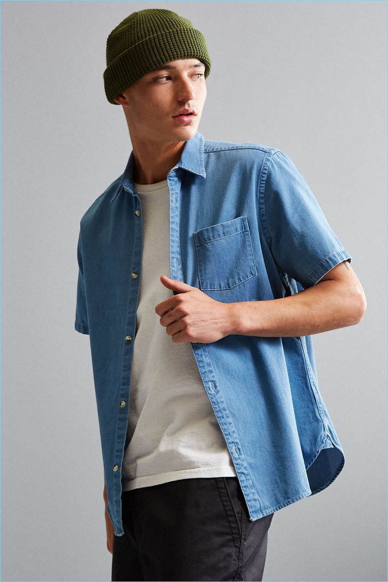 Versatile short sleeve button-down shirt from Urban Outfitters in classic cotton denim. Cut in a standard fit with a pointed collar, full-length front button closure and rounded hem. Finished with a front patch pocket.