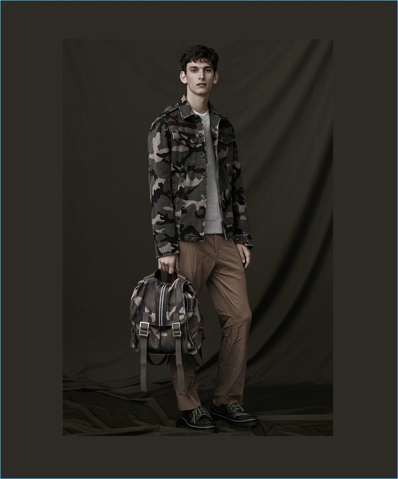 Front and center, Thibaud Charon wears a jacket with a complementary camouflage backpack by Valentino.