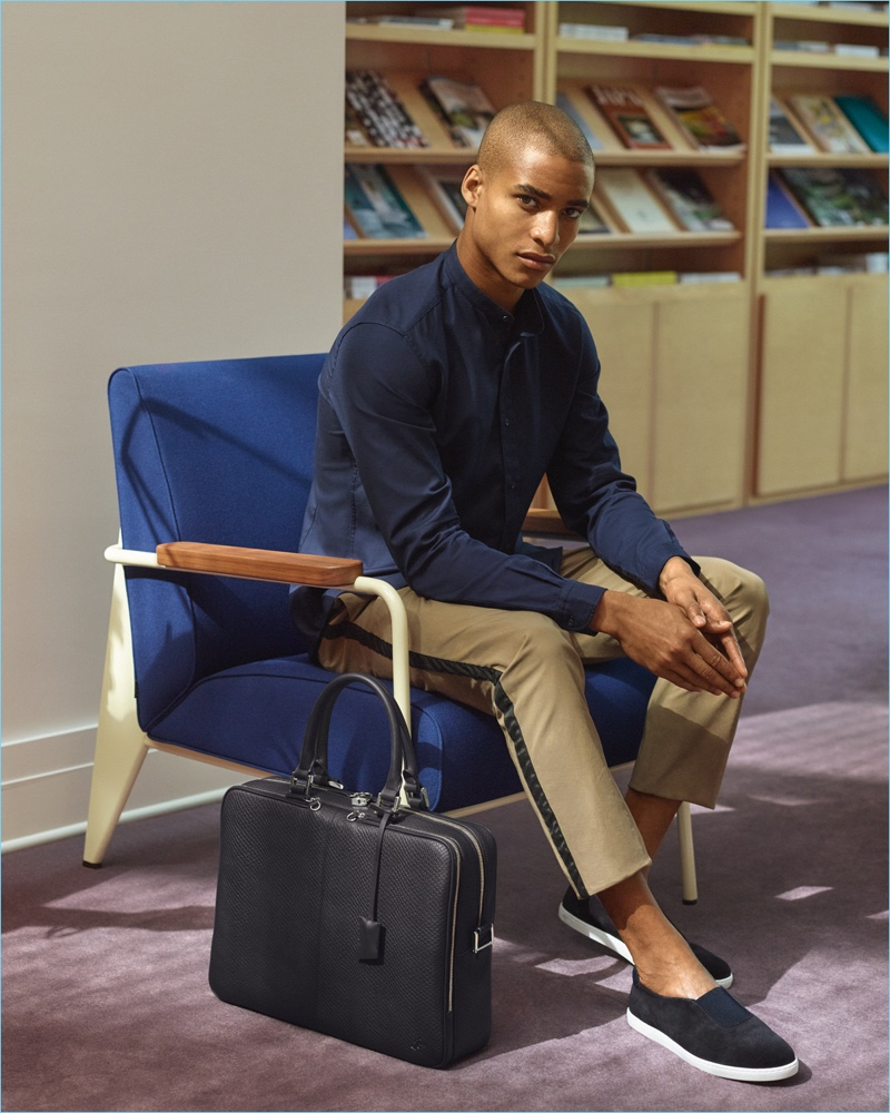 Model Malik Lindo wears WANT Les Essentiels' suede shoes, which complement the brand's leather briefcase.