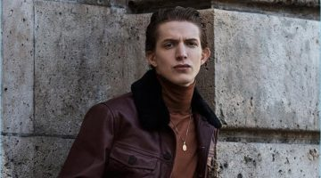 Model Xavier Buestel wears a Kenzo leather jacket with a Berluti turtleneck. The top model also rocks jeans, a leather belt, and necklace by Paul Smith.