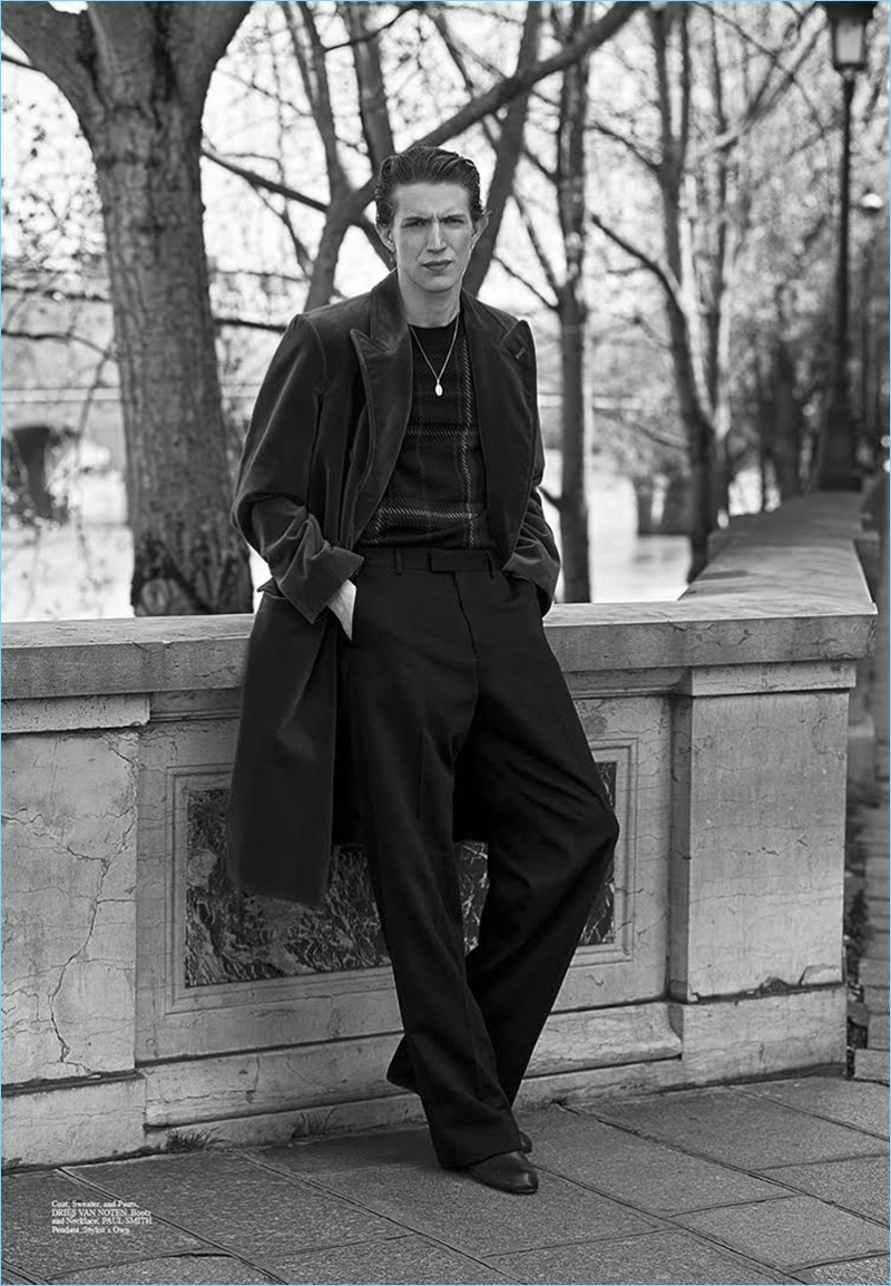 Embracing oversized proportions, Xavier Buestel wears a coat, sweater, and trousers by Dries Van Noten. Xavier also sports boots and a necklace by Paul Smith.