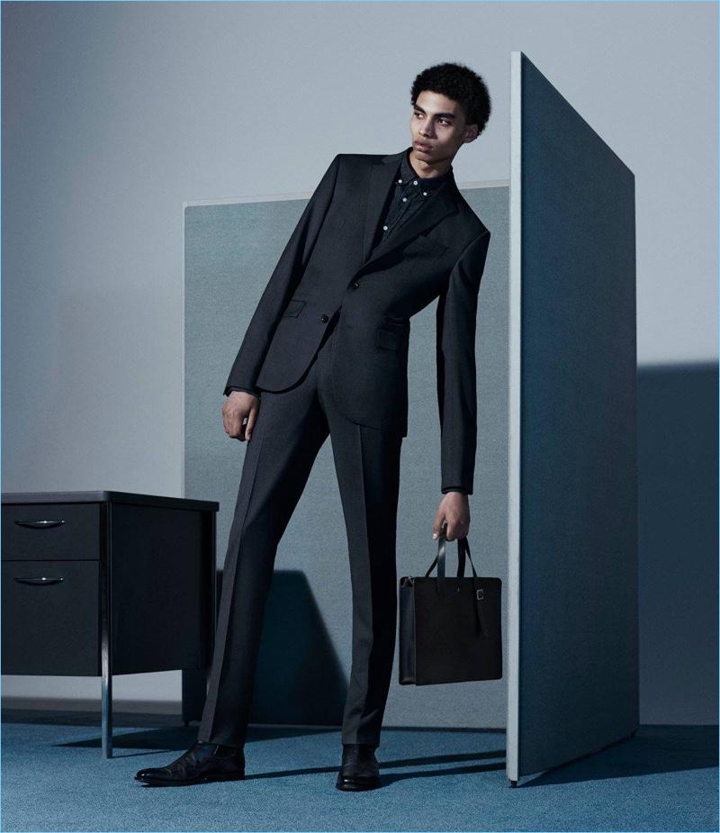 Wearing a grey Barneys New York suit, Sol Goss also dons an Officine Generale selvedge denim shirt, Crockett & Jones Chelsea boots, and a Serapian briefcase.