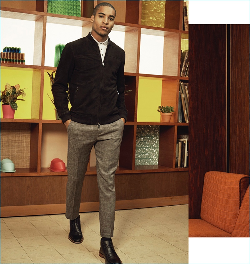 Malik Lindo embraces smart style with a bomber jacket, polo, and trousers by Ted Baker. Malik's look is complete with a pair of John Varvatos Star USA Chukka boots.