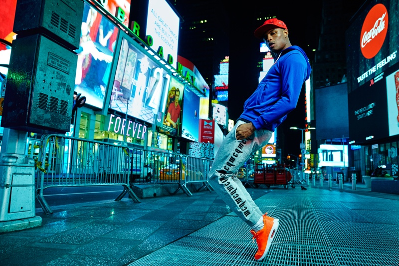 Isaiah wears hoodie Comme des Garçons, pants Alexander McQueen, hat stylist's own, and shoes Nike.