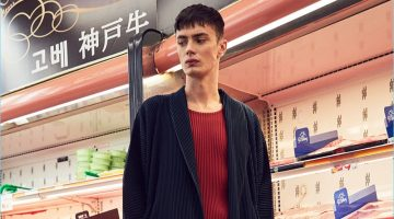 Embracing a draped silhouette, Simon Kotyk dons an Issey Miyake Homme Plisse long jacket with a red shirt and pleated cropped trousers. Simon's look is complete with Acne Studios leather sneakers.