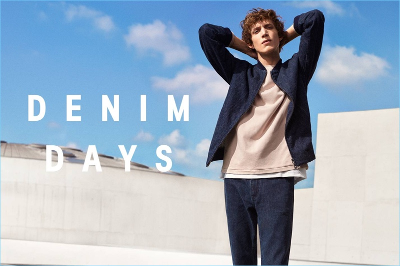 Xavier Buestel wears a denim bomber jacket, wide-cut sweatshirt, cotton piqué t-shirt, and jeans from H&M.